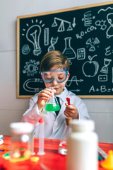 Boy dressed as chemist playing with chemistry game in front of a blackboard with drawings