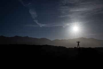 human dark silhouette doing strength pose on the mountain during the sunrise with back light
