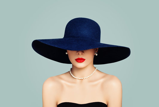 Elegant woman fashion model with red lips makeup wearing classic hat and white pearls, portrait