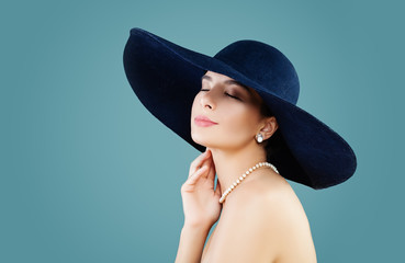 Sensual woman fashion model in hat on blue background with copy space