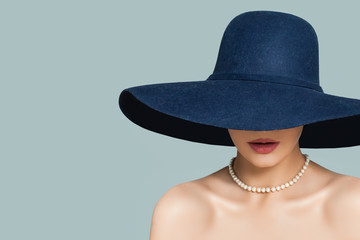 Perfect woman in fashionable hat and white pearls jewelry necklace on blue background