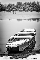 Beautiful frozen river. A boats covered with snow. Black white photo