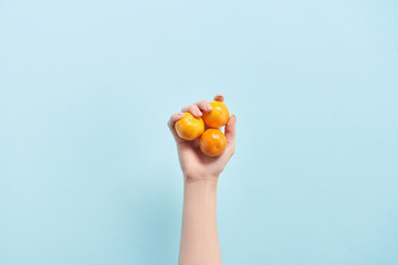 cropped view of woman holding orange tangerines in hand isolated on blue