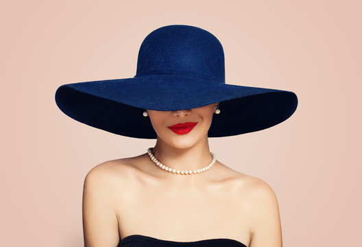 Beautiful smiling woman in elegant hat on pink background. Stylish girl with red lips makeup, fashion portrait