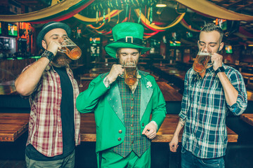 Picture of three young man stand together in pub and drink beer from mugs. They concentrated. Guy on middle wear St. Patrick's suit.