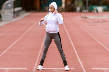 Beautiful sporty woman putting hoodie on while standing on the racetrack.