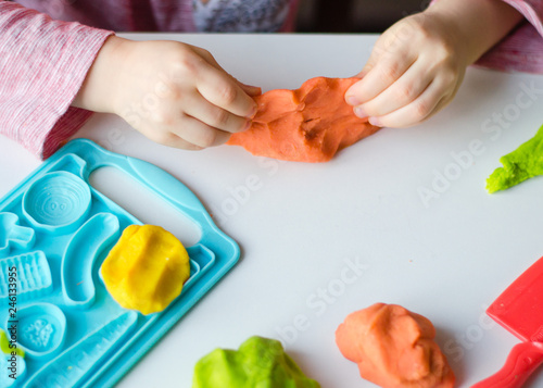 Child's hands with colorful clay. Child playing and creating vagetables from play dough. Girl