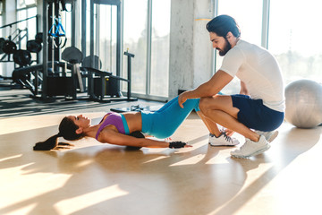 Slim Caucasian sporty woman with ponytail doing exercises while personal trainer crouching next to her and helping her.