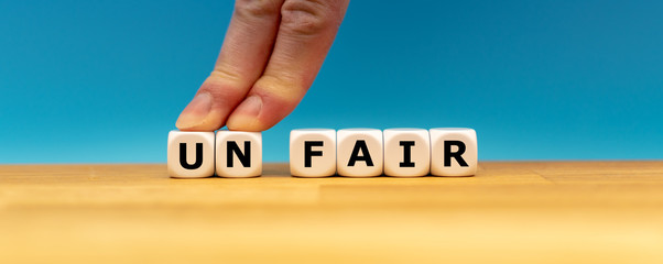 "Dice form the word ""UNFAIR"" while two fingers push the letters ""UN"" away in order to change the word to ""FAIR""."