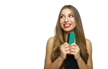 Portrait of a lovely young woman showing credit card and looking away at copy space isolated over white background