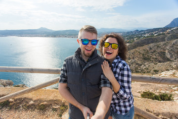 Travel, vacation and holiday concept - Beautiful couple having fun, taking selfie, crazy emotional faces and laughing.