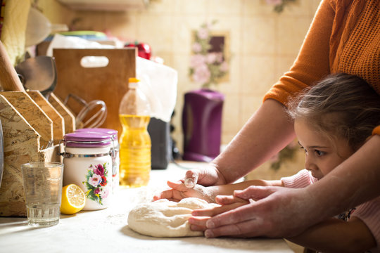 little girl helps mom to make bread
