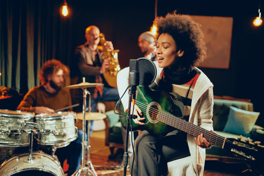 Mixed race woman singing and playing guitar while sitting on chair with legs crossed. In background drummer, saxophonist and bass guitarist.