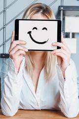 giovane donna fa finta di sorridere con tablet davanti al viso