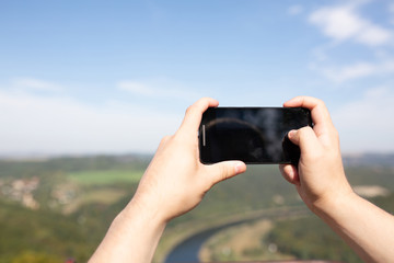 Male hands holding his mobile phone outdoor, taking a photo in the landscape park