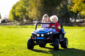 Kids driving electric toy car. Outdoor toys.