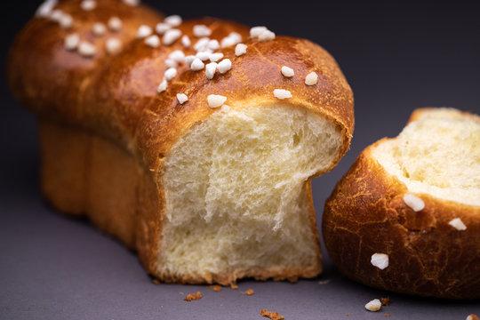 Freshly brioche bread with pearl sugar on black background