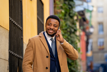 Portrait of handsome african american businessman walking in the city talking on mobile phone