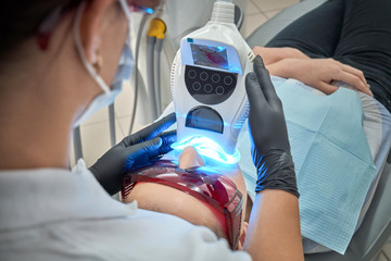 Hands of dentist keeping equipment radiating ultraviolet