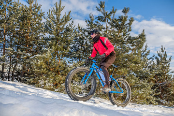Man riding a mountain bike with big fat tires and helmet on a snow. Fat bike.