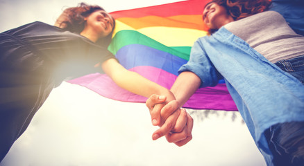 beautiful female young lesbian couple in love holding hands, and a rainbow flag, a symbol of the LGBT community, equal rights, beauty and love Wall mural