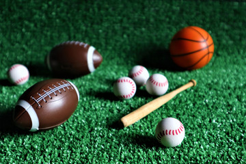 collection of several sport game balls such as football, soccer, and tennis, flying on a green background.