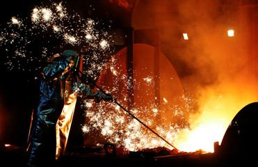 A steel worker of Germany's industrial conglomerate ThyssenKrupp AG stands amid emitting sparks of raw iron from a blast furnace at Germany's largest steel factory in Duisburg