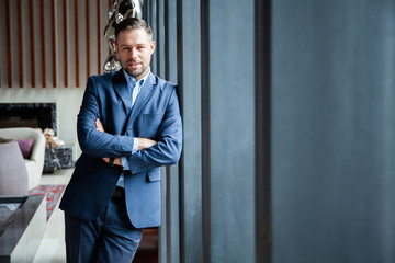 Businessman portrait. Happy confident young businessman standing arms crossed, smiling, looking at camera