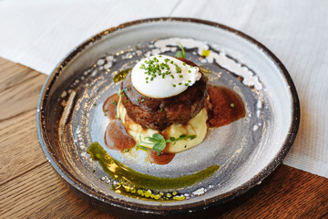 Meat cutlet on a pillow of mashed potatoes with poached egg on top, poured with pesto and teriyaki with meat sauce, decorated with green onions.