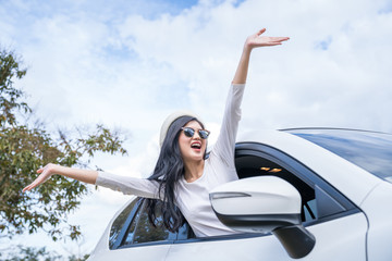 Young woman relax and happy on summer road trip travel vacation leaning out car window on blue sky.