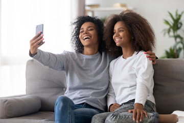 Happy millennial black mom make selfie on smartphone with teenage daughter, smiling mother and teen child shot self portrait picture on cell phone at home. Concept of parent and children relationships