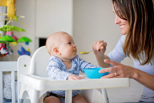 Cute little baby boy, eating mashed vegetables for lunch, mom feeding him
