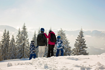 Beuatiful family with two kids, skiing on a sunny day in scenery austrian Alps
