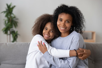 Portrait of happy African American mom and teen daughter spend time at home together, hugging on couch, smiling teenage girl embrace young black mother or nanny, show love and affection