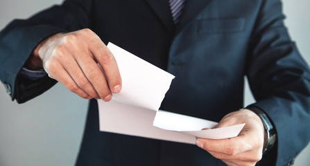 Businessman tearing white blank paper.
