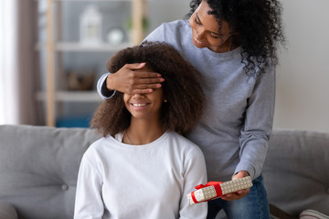 Excited black young mom make surprise for teenage daughter, happy African American mother close child eyes, presenting birthday gift, relaxing at home together, mommy congratulate kid