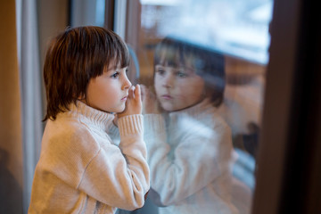 Preschool boy, sitting by the window in living room, looking at a snowy landscape