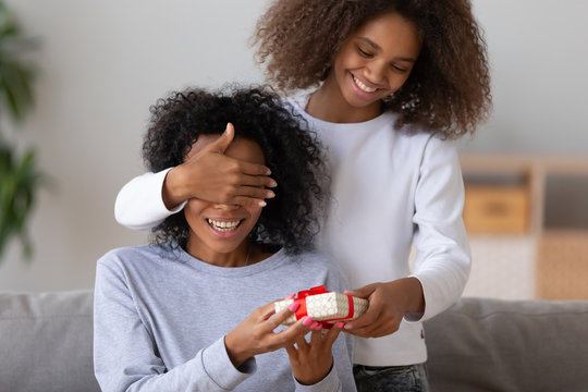 Excited African American daughter close mom eyes, making birthday surprise, happy black teenage girl give present to mother on special occasion or anniversary, smiling mommy receive congratulation box