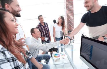 handshake of colleagues in a creative office.