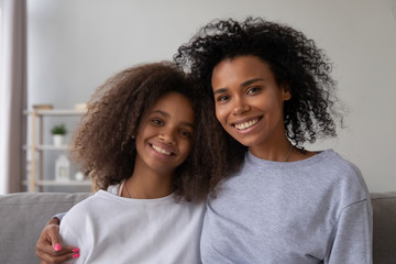 Portrait of happy African American mother and daughter hug sitting on couch at home, smiling black mom or nanny embrace teenage girl, spending time together, looking at camera posing for picture