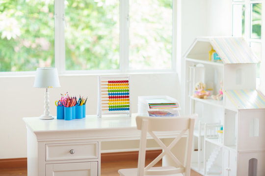 Kids bedroom with wooden desk and doll house.