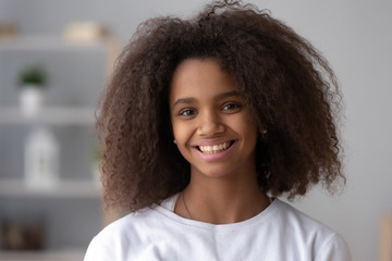 Portrait of happy African American teen girl looking at camera at home, headshot of smiling black teenager posing indoors, beautiful mixed race teenage female laughing making picture