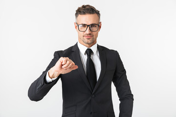 Handsome business man isolated over white wall background posing looking at watch clock.