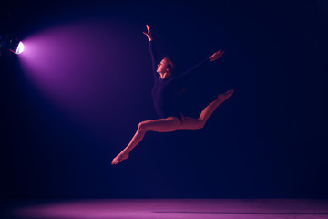 Young female ballet dancer dancing on neon lights studio background. Ballerina project with...