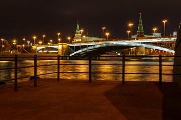 View of Bolshoy Kamenny Bridge and Moscow Kremlin with night illumination on a background of pleasure boats pier