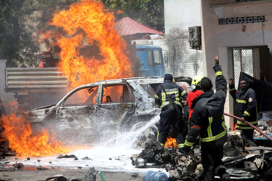 Somali firemen try to extinguish burning cars at the scene where a car bomb exploded in front of a restaurant in Mogadishu