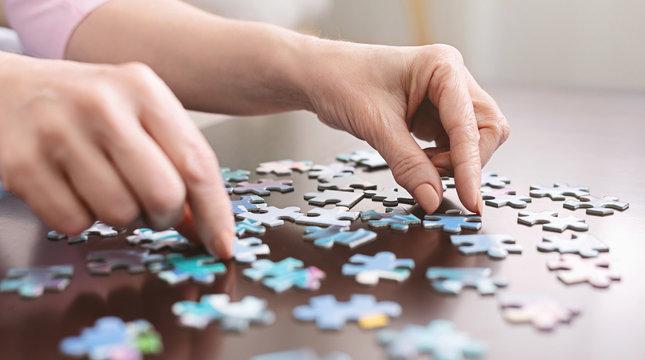 Elderly woman hands doing jigsaw puzzle closeup
