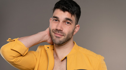 Handsome caucasian white male with black short hair and stubble with yellow jacket