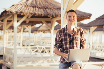 Portrait of a positive young remote worker guy with a laptop sitting under a straw canopy on the beach on a sunny summer day. Freelancer and outsourcing concept