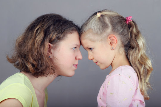 Two sisters stand opposite each other, make eye contact.